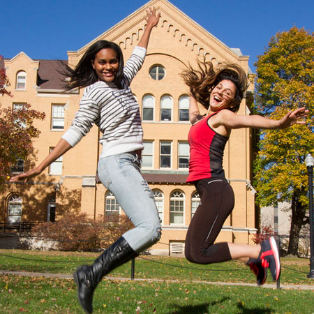 NIU students jumping in front of Williston Hall.